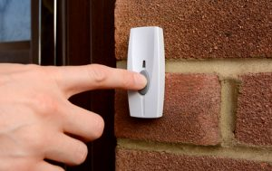 47237659 - close-up of woman pressing the button of a doorbell on a brick wall